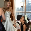 Bride and Flower Girl look at each other Laughing, now in their dresses