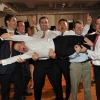 Groom held Horizontally by Friends, arms outstretched